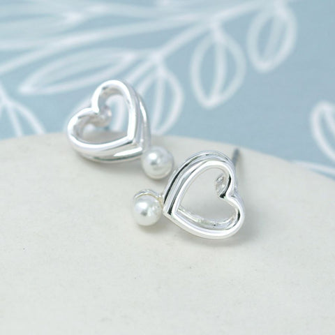 Double layer heart stud earrings with white faux pearls.