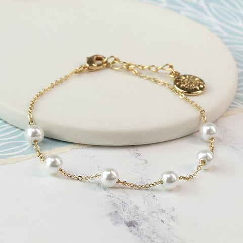 Delicate gold plated bracelet embellished with white glass pearls.