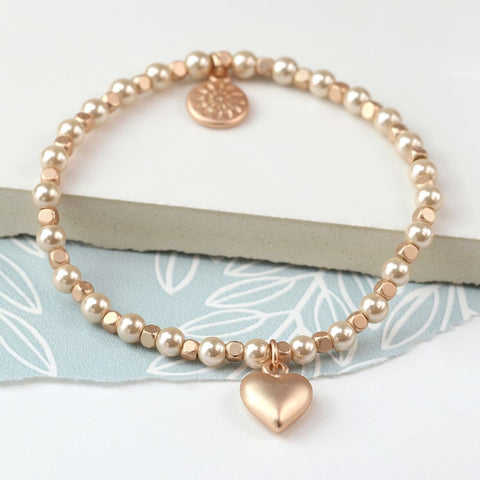 Pretty stretch bracelet made from matt rose gold cube beads and champagne coloured faux pearls, with a heart charm in a rose gold style matt finish.