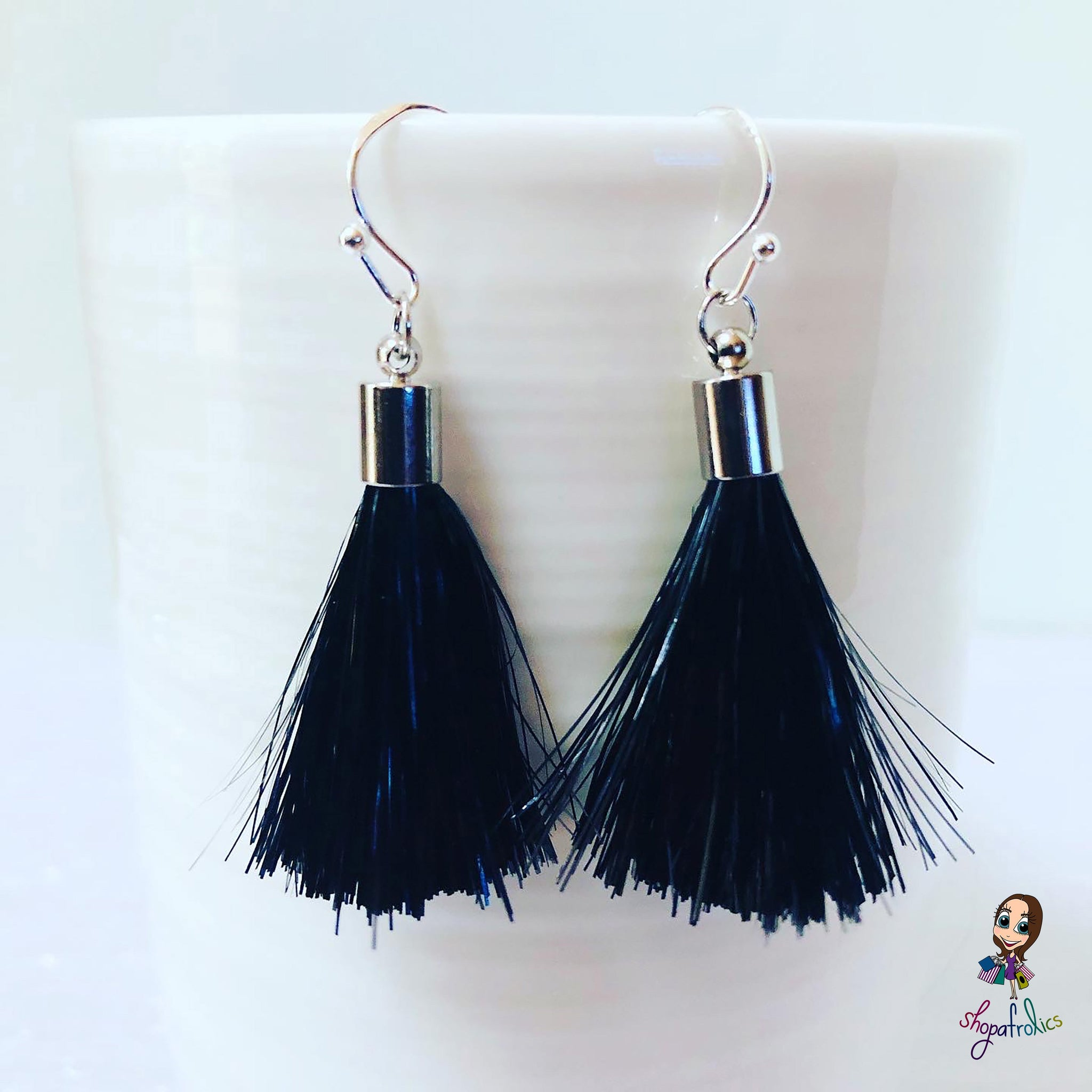 Close up of black and silver tassel earrings