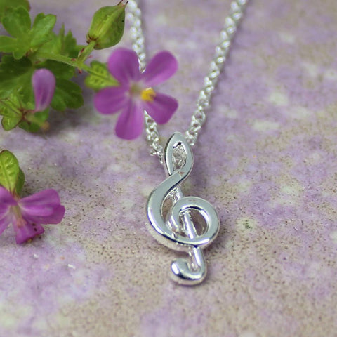 Dainty treble clef necklace plated in pure silver.