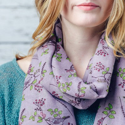 A beautiful bird print design scarf on a solid coloured background and finished with a feathered edge