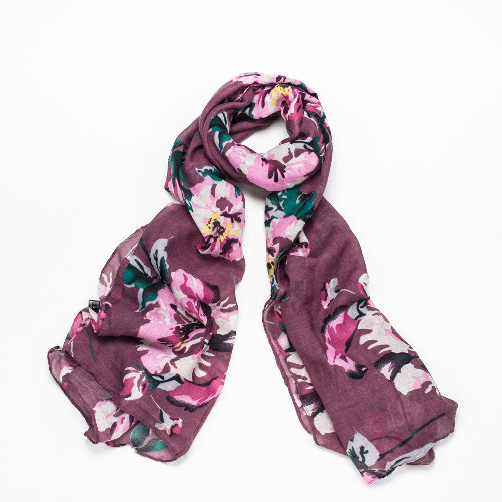 A lovely purple scarf with large pink flower detail and finished with a rolled edge