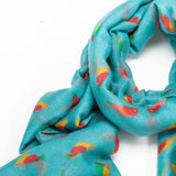 Vibrant bird printed scarf on a bright green background with feathered edge