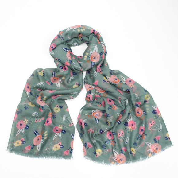 Delicate pastel pink flower printed scarf on a green background with feathered edge