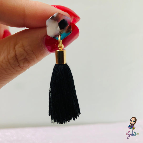 Close up of one black cotton tassel drop earrings are finished with a vibrant coloured hexagon acrylic ear stud.