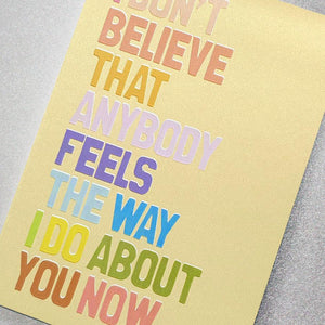 A gorgeous golden glitter effect greeting card with rainbow lettering featuring the slogan: I don't believe that anybody feels the way I do about you now