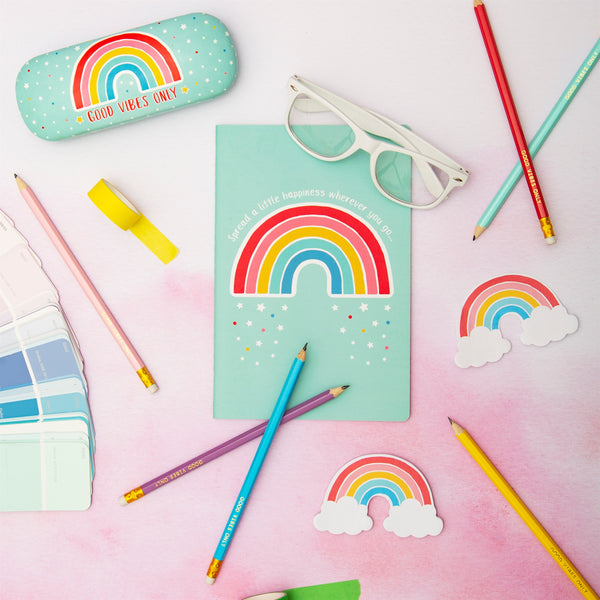 Rainbow notebook with slogan spread a little happiness wherever you go flatly