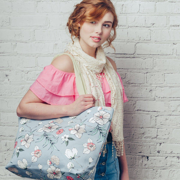 Large canvas bag with vibrant delicate floral design print, on a solid blue coloured background