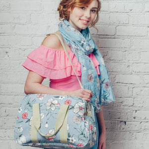 A versatile canvas weekend bag in vibrant delicate floral design print, on a solid blue coloured background. A mini break essential!