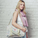 A versatile canvas weekend bag in vibrant delicate floral design print, on a solid grey coloured background. A mini break essential!
