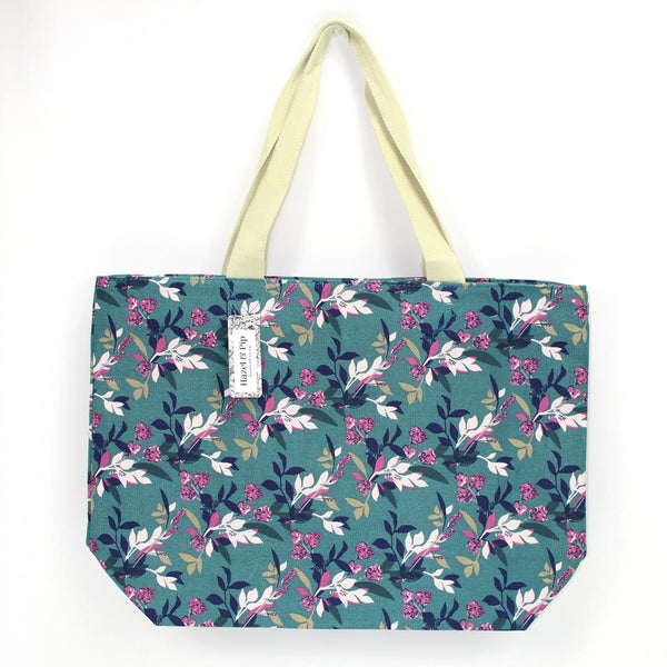 Large canvas bag with vintage style floral print, on a solid green coloured background