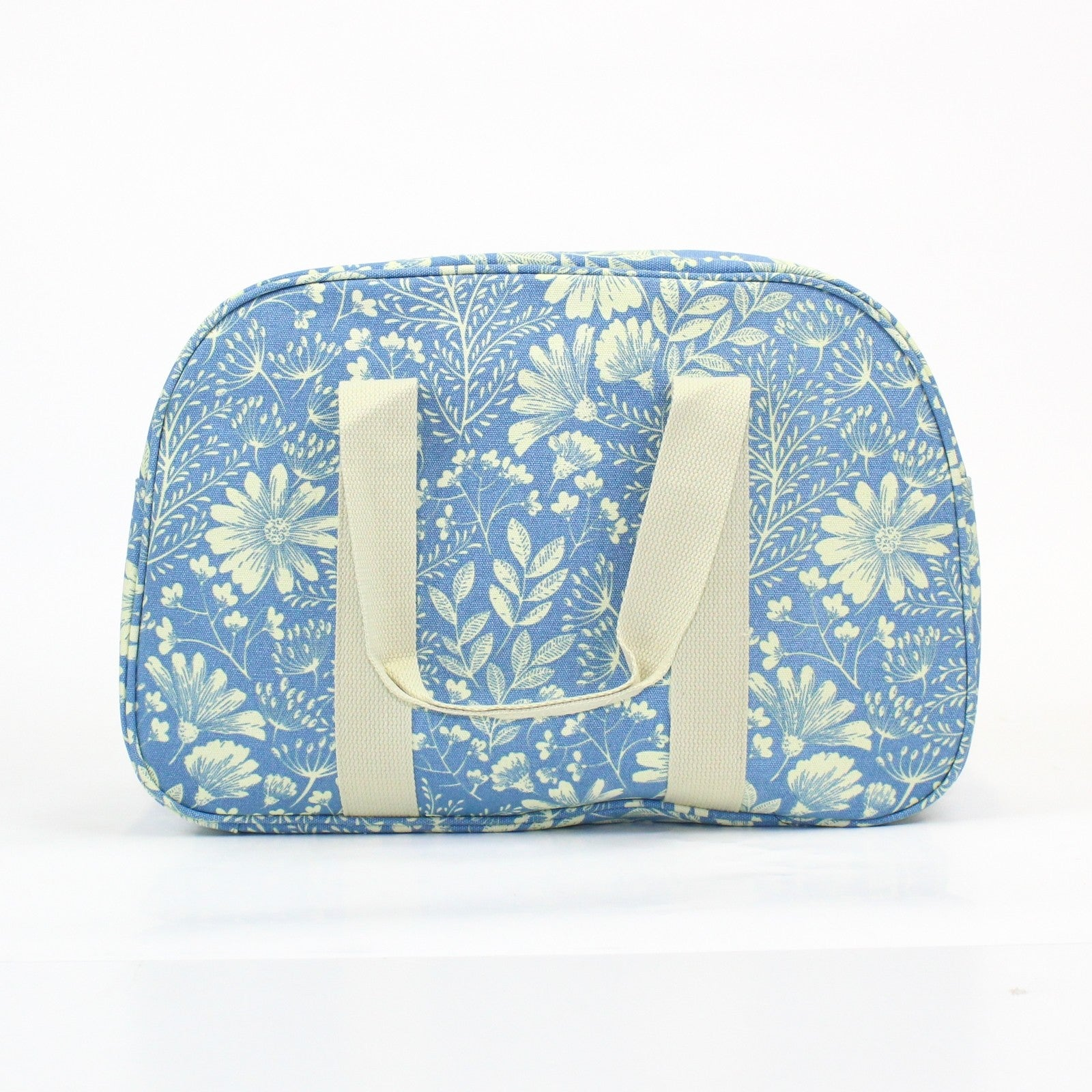 Pretty floral print weekend bag, on a light powder blue background.
