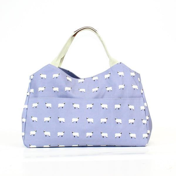 Fun and multi-functional sheep print day bag, on a solid lilac purple coloured background.