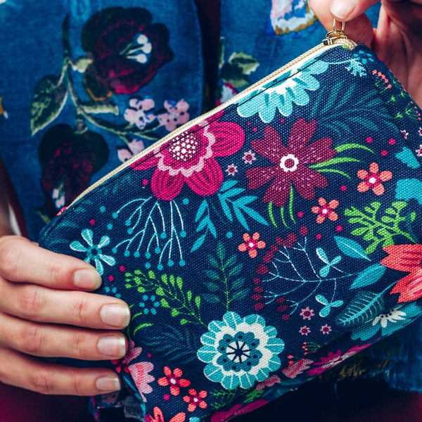 Make up bag in bold blue and pink floral design on a dark background