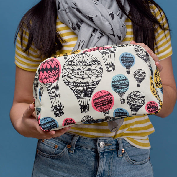 Large oil cloth make up / wash bag with colourful hot air balloon print, on a solid white background.