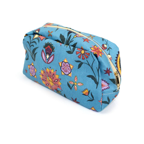 Large oil cloth make up / wash bag with a pretty paisley print with a boho vibe, on a solid blue background.