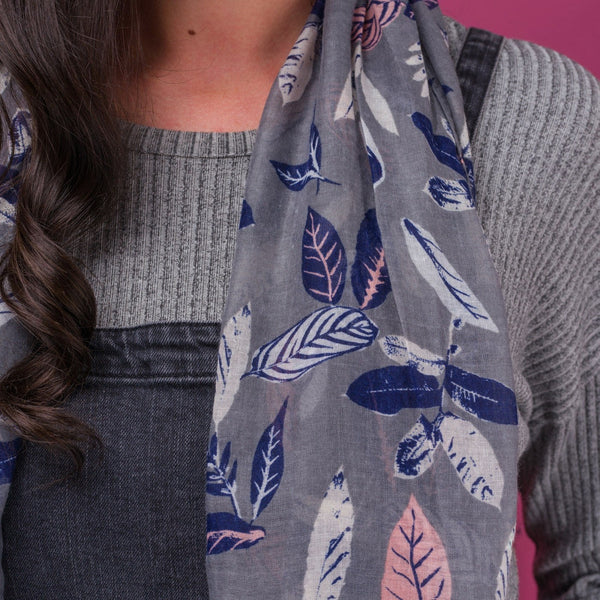 Close up of Pretty vintage leaf print scarf on a solid grey coloured background and finished with a rolled edge