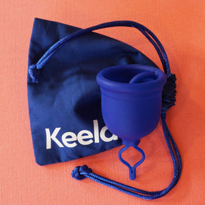 "A picture of the blue Keela Cup sitting on top of it's blue drawstring bag which reads ""Keela"". These items are on a textured orange background."