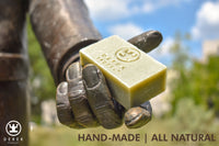 A statue holding a hand made all natural bar soap from Derek Products