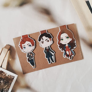 A photo of Wylan Van Eck, Nina Zenik, and Kaz Brekker magnetic bookmarks by IdleStuff on brown paper with books and a mini easel on top of plain white sheets.