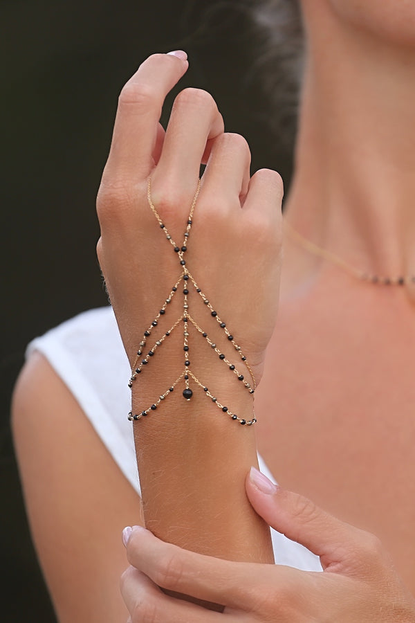 layer a black hand chain bracelet with a dainty necklace
