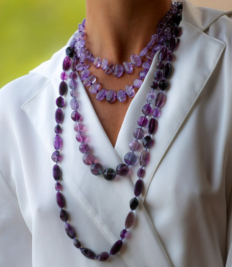 layer several purple and violet gemstone necklaces