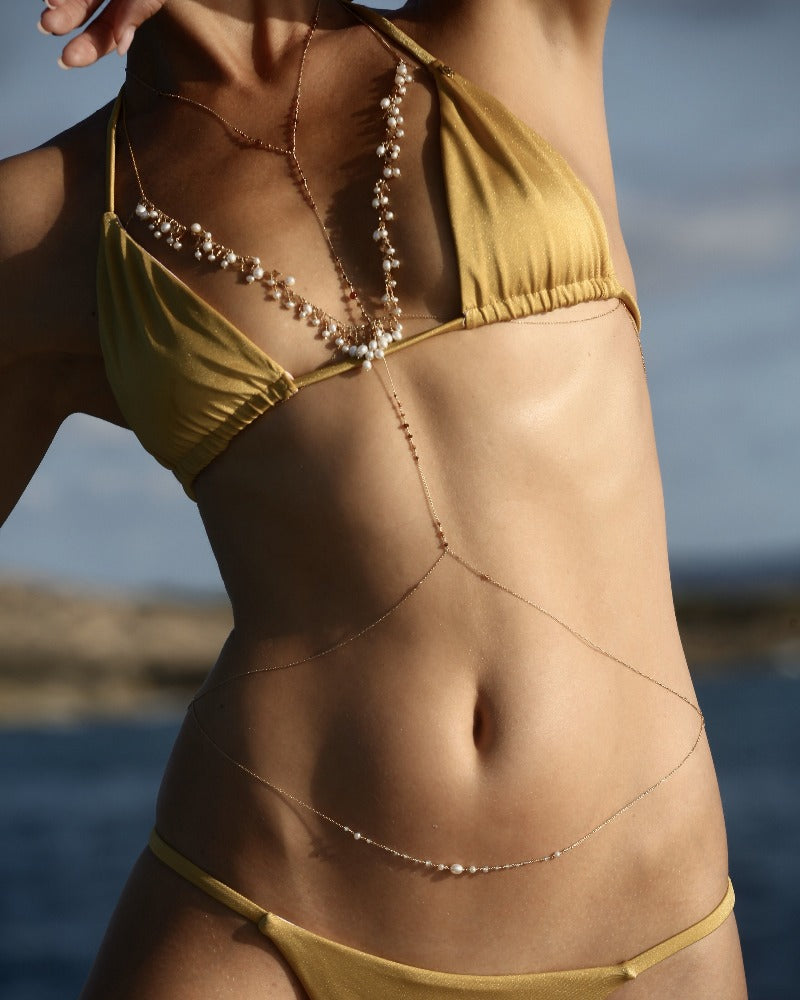 layer body jewelry with pearls on the beach