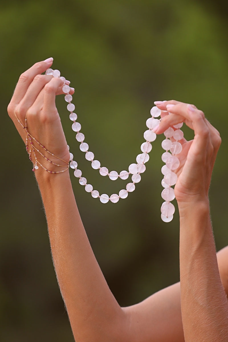 wear a pink hand chain with a rose quartz neckalce