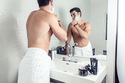 Man in Towel Using A Straight Razor to Shave in Mirror | Style Standard