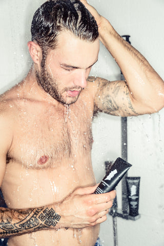 Man with Tattoos in Shower Holding Facial Scrub Bottle | Style Standard