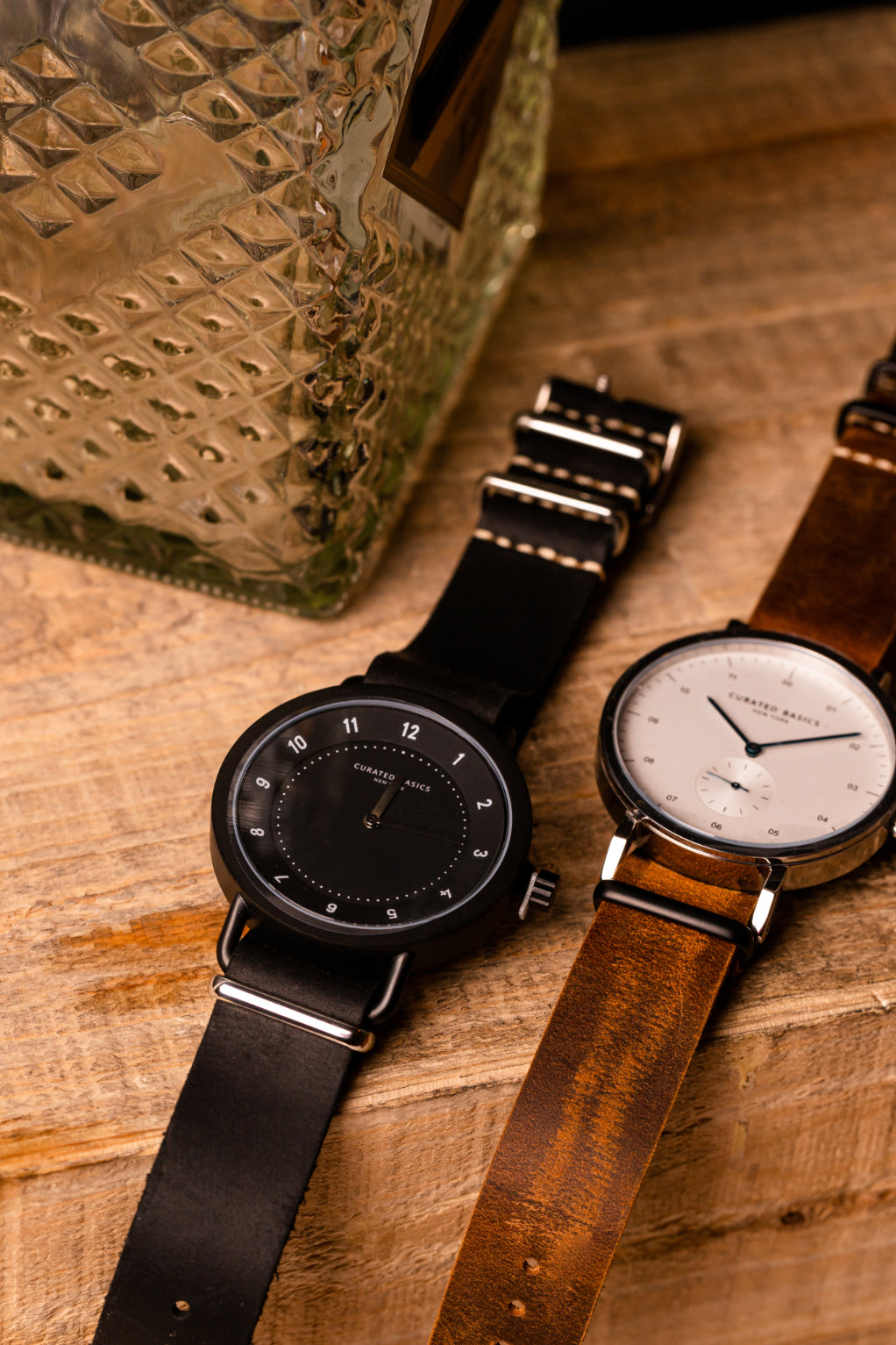 The Chuck Watch on A Black Leather Strap and The Oliver Watch on a Brown Leather Strap Over A Wood Block With An Empty Decanter Behind   Style Standard