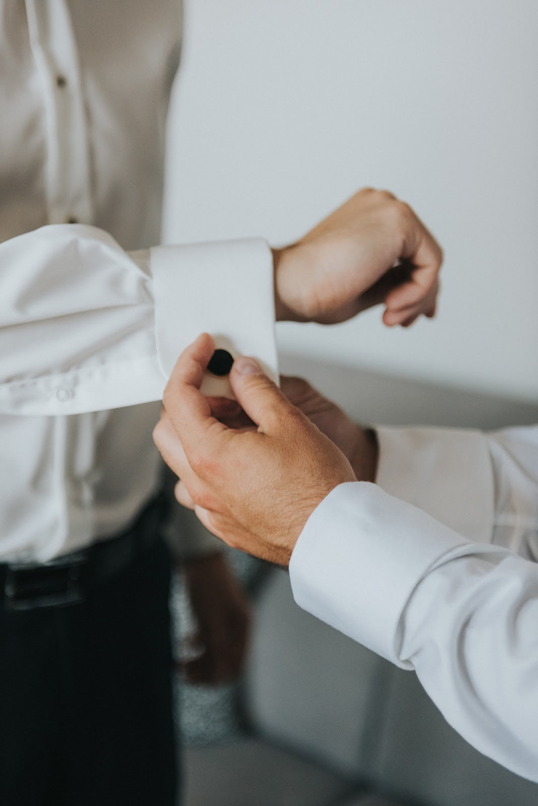 Man's hands in white shirt helping to adjust cufflink on another man in white tuxedo shirt | Style Standard