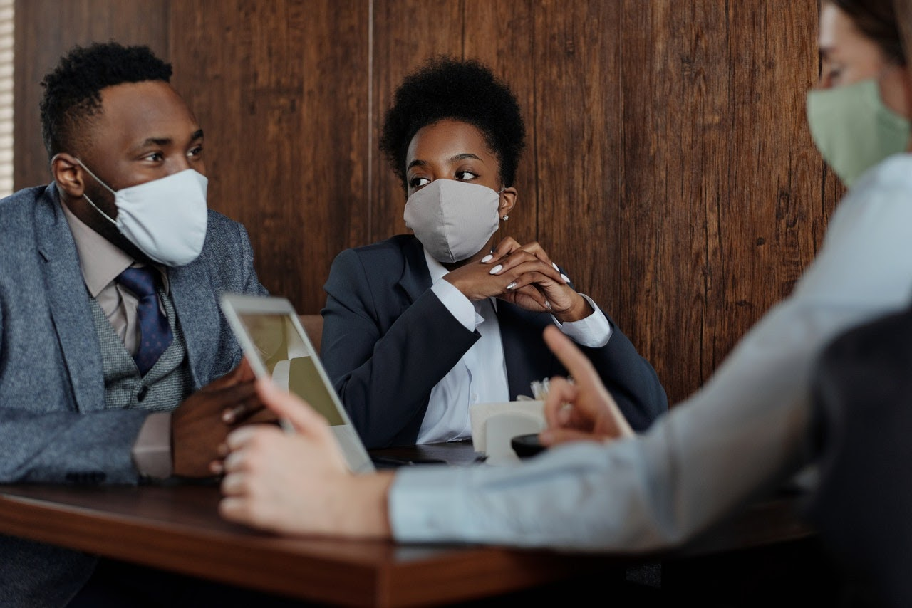 Three people sitting around a table wearing face masks and business casual attire