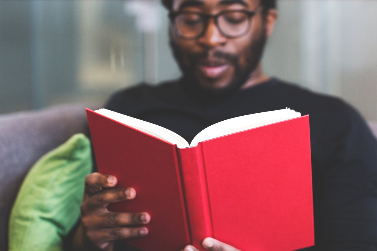 Black man with beard and glasses reading a hardcover red book | Style Standard