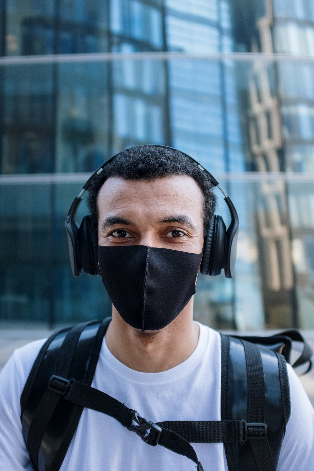 Man in white t-shirt with black backpack wearing a black face mask and headphones in front of a glass building | Style Standard