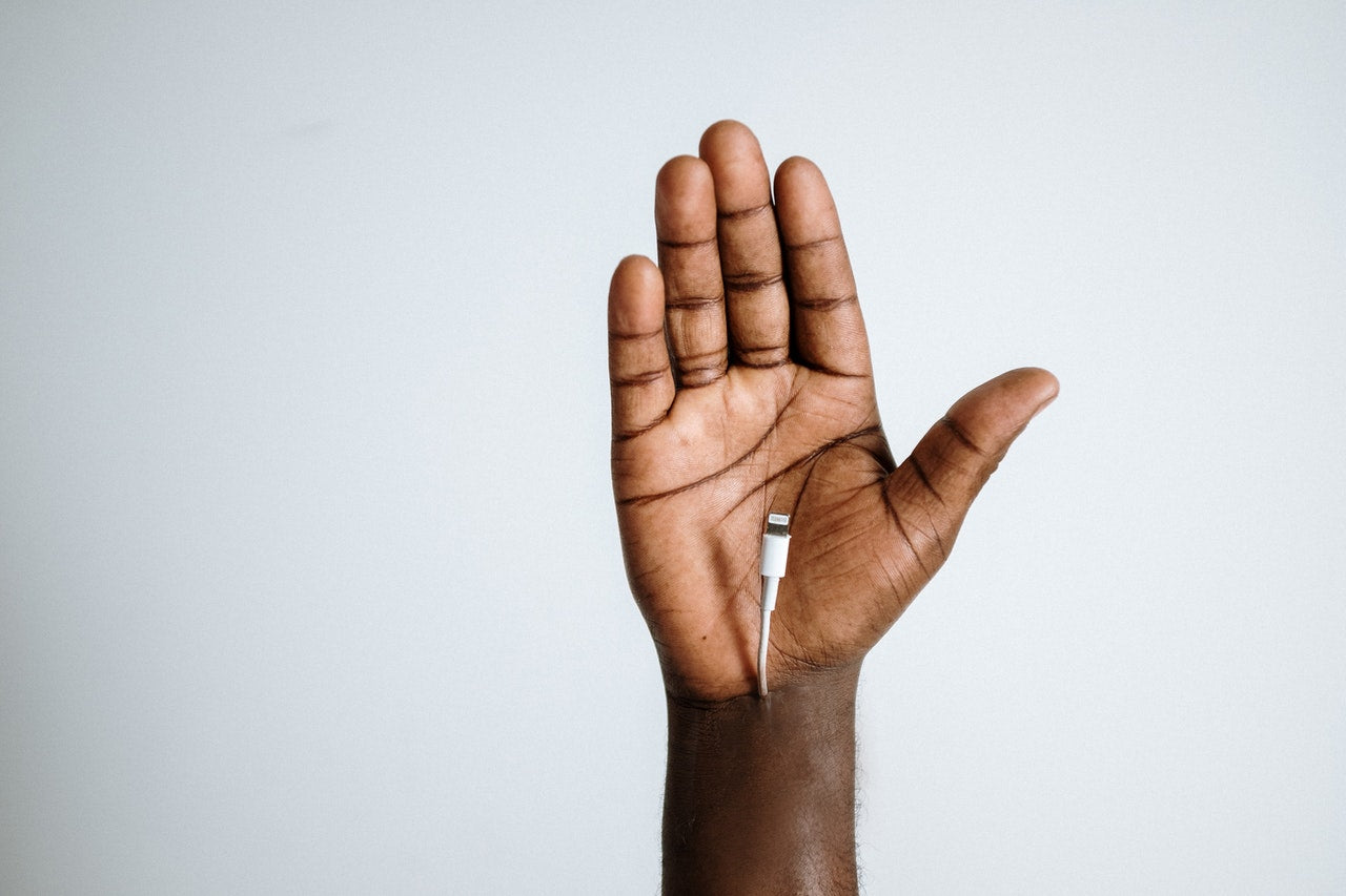 Black Person's Hand Raised with Palm Facing Camera and Charging Cable Coming From The Wrist   Style Standard
