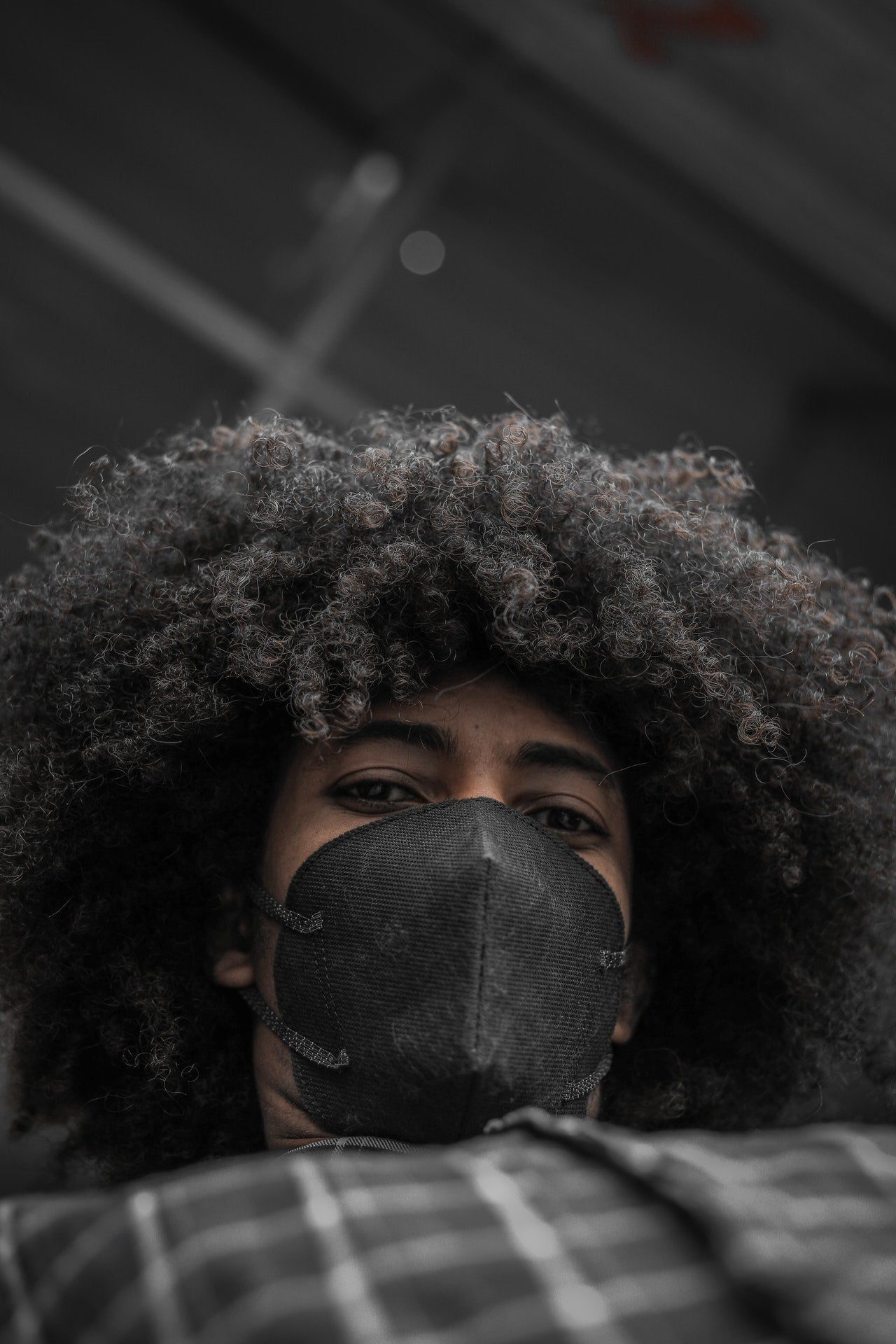 Black person with large hairstyle wearing a black facemask and dark shirt looking down into the camera