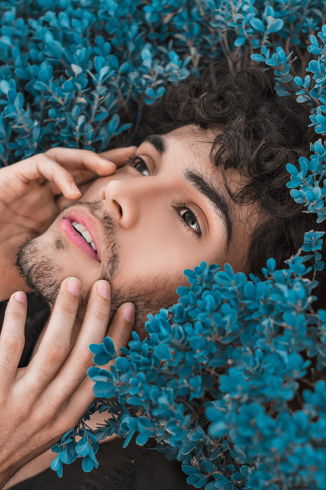 Man Touching Face Surrounded by Blue Foliage | Style Standard