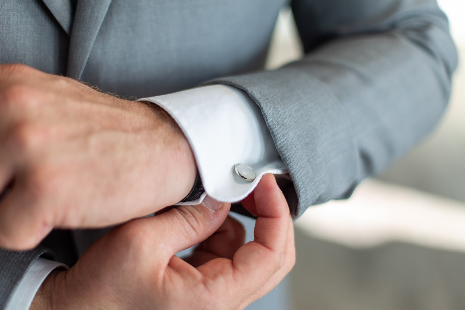 Man in Light Grey Suit Fixing Cufflink on White Shirt | Style Standard