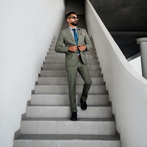Man in green suit walking down white stairs | Style Standard