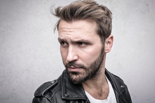 Man with short-medium length hair in white t-shirt and leather jacket looking off camera | Style Standard
