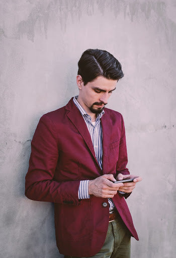 Man with goatee in red blazer, green chinos, and light striped shirt leaning against a wall and checking his phone   Style Standard