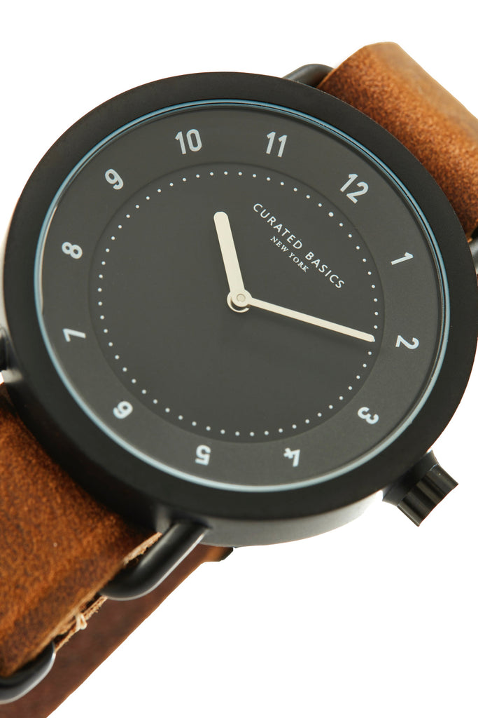 Angled Closeup of The Chuck timepiece, a black watch on a brown leather strap over a white background