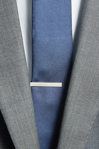 Navy Solid Tie with Brushed Steel Tie Bar behind a grey suit on a white shirt