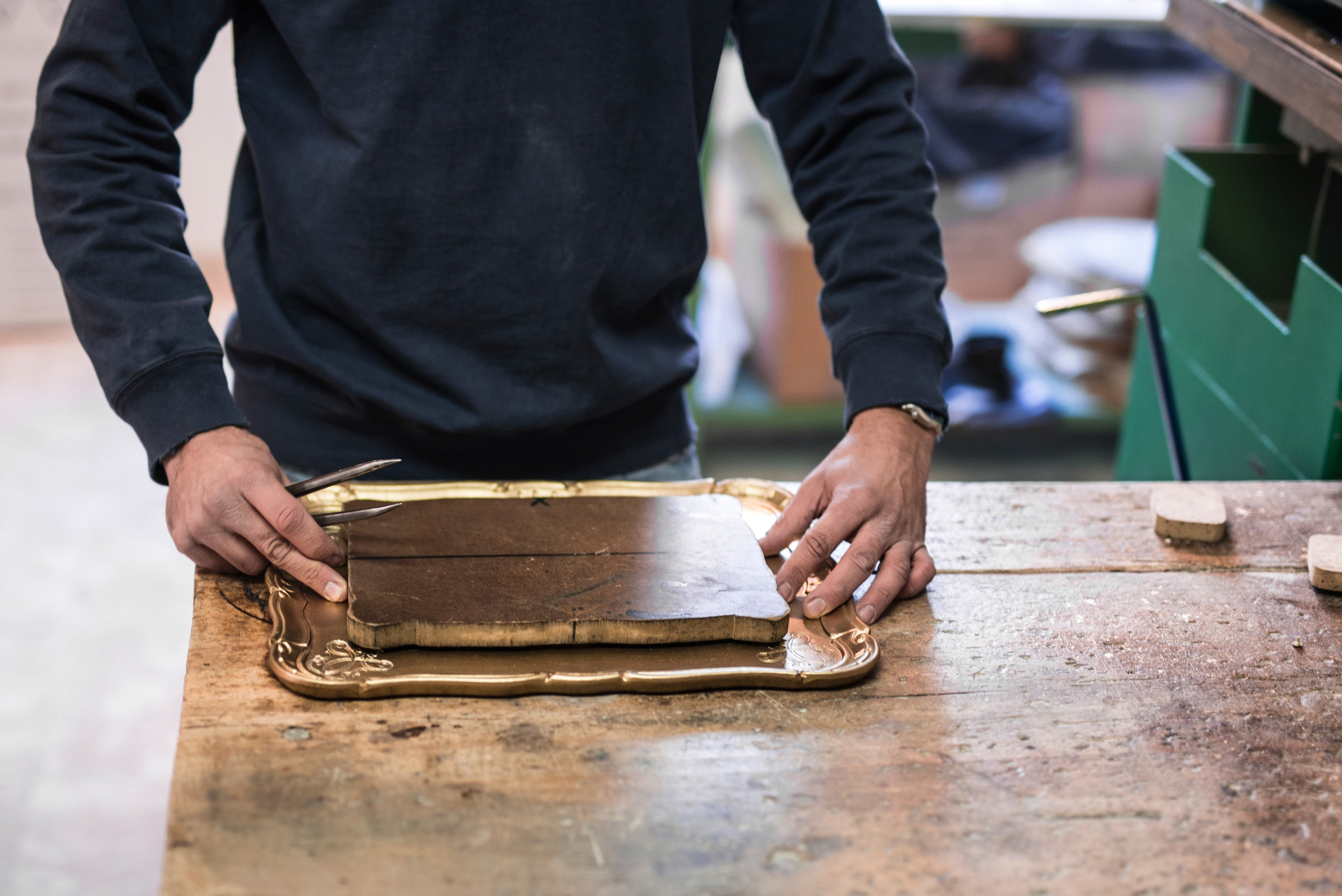 Artisan imprinting design on wood tray in R+D.LAB Florence Lab