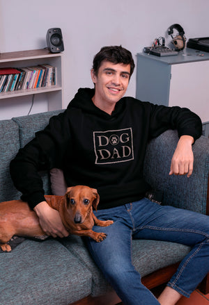 Photo-of-a-man-sitting-on-a-couch-with-his-dog-Black-hoodie-WearPet-DOG-DAD