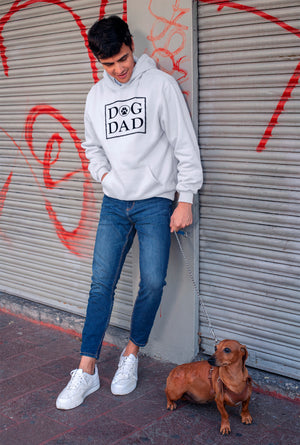 Photo-of-a-man-wearing-a-white-hoodie--leaning-on-a-graffiti-wall-with-his-dog-WearPet-DOG-DAD