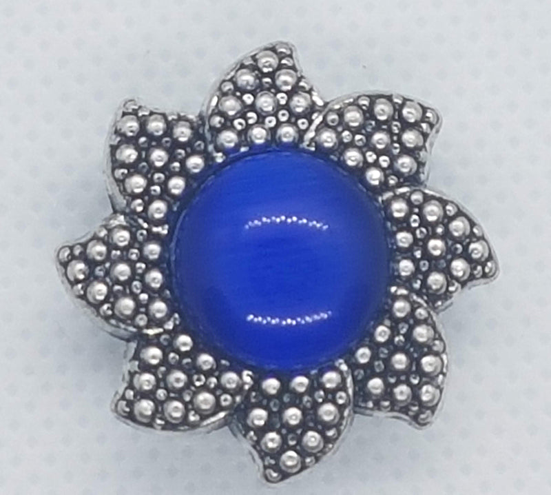 Flower shaped snap with large blue stone