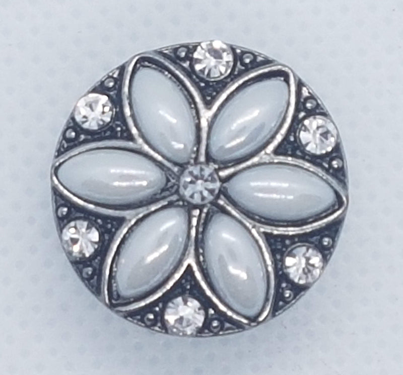 Round snap with white flower shaped stones and clear rhinestones